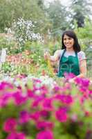 Woman having fun while watering plants with hose