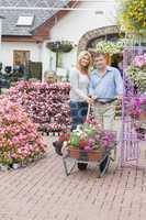 Couple pushing a trolley in garden center
