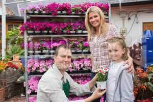 Employee presenting flower pot to little girl with mother