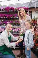 Employee giving flower pot to little girl with mother
