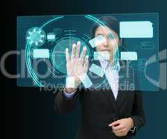 Businesswoman standing while touching at a hologram