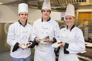 Three Chef's presenting cakes
