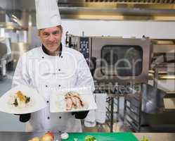 Chef holding two plates in the kitchen