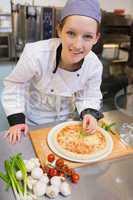 Smiling chef preparing pizza