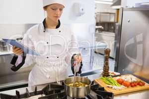 Woman viewing tablet pc while cooking