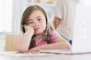 Child sitting at the table looking bored