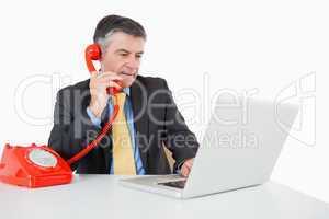 Serious man phoning while writing on laptop