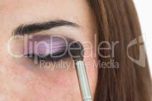 Pale woman getting smoky eyes