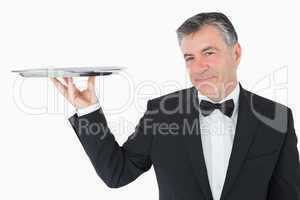 Well-dressed waiter holding a silver tray