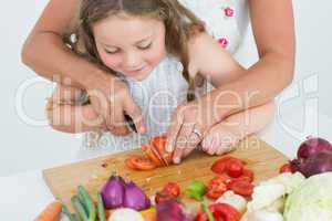 Mother helping her daughter to cut tomato