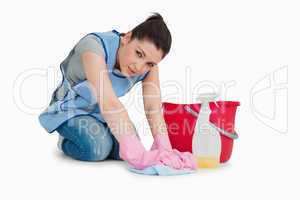 Exhausted cleaning woman wiping up the floor