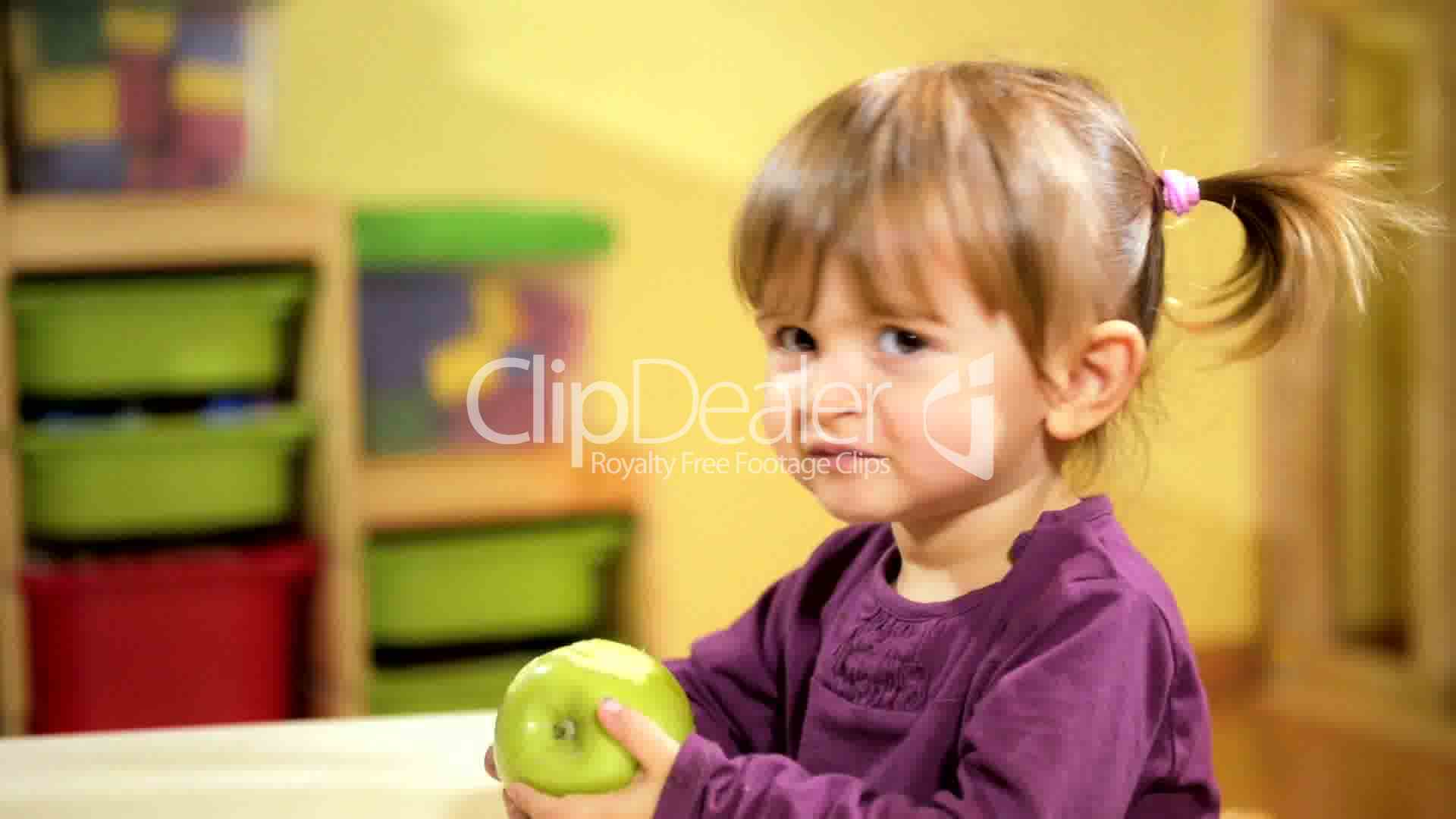 babies and food, female child eating green apple in kindergarten