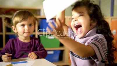 Preschool and fun, happy kids drawing in kindergarten