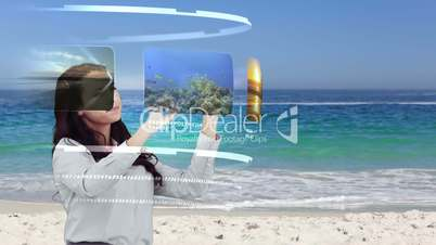 Woman looking at holiday activities on interactive media library on beach