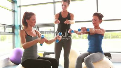 Women lifting weights on exercise ball with trainer
