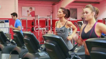 Three persons running on a treadmill