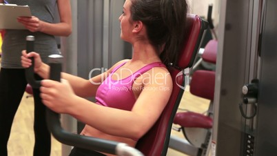 Woman on weights machine talking to trainer