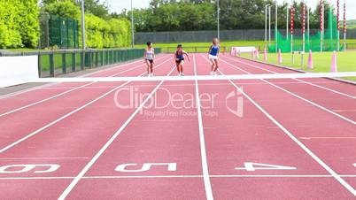Three woman running on a track and crossing finish line