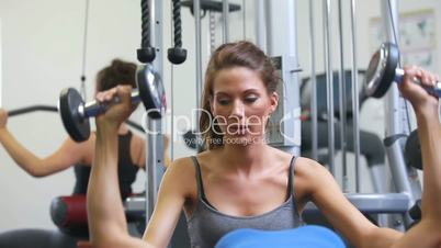 Trainer helping lying woman lifting weights