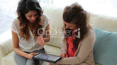 Woman showing friend tablet tc