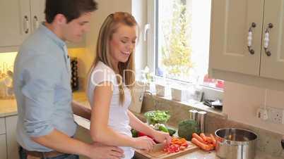 Man embracing wife preparing vegetables