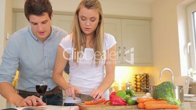Woman cutting vegetables with man reading cookbook