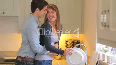 Man coming in behind woman as she is washing up