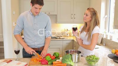 Man is cutting vegetables with woman drinking wine then kissing