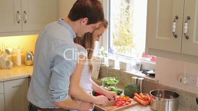 Woman is cutting vegetables with man standing behind her