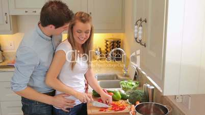 Woman cutting vegetables with man coming in to hug her
