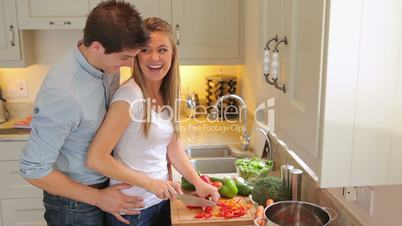 Woman cutting salad with man holding her from behind