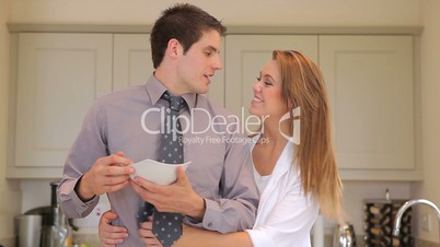 Man eating cereal then wife is hugging him
