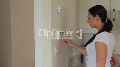Woman turning on home alarm system