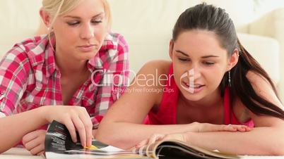 Women lying looking through magazine