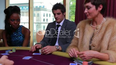 People being dealt poker cards with two people folding and one placing bet