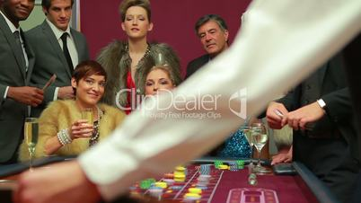 Women winning at roulette and cash falling on them