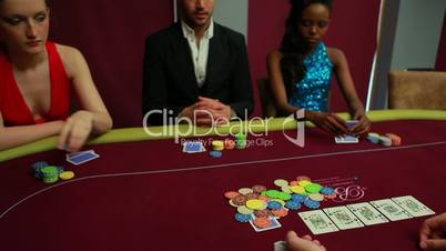 People placing their bets at poker game