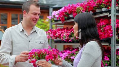 Man and woman standing in front of a flower shelf