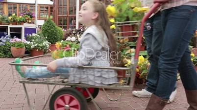 Little girl being pushed in trolley at garden center