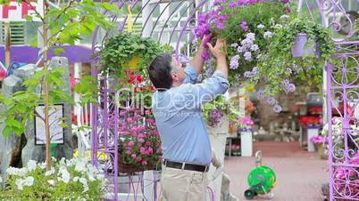 Man is smelling flowers in hanging basket
