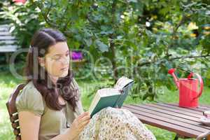 Junge Frau liest im Garten, young woman reading in a garden