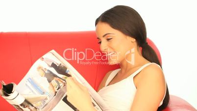 Woman reading a magazine on a sofa