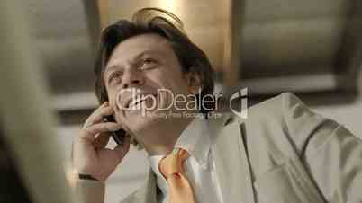 Adult business man in office talking on telephone