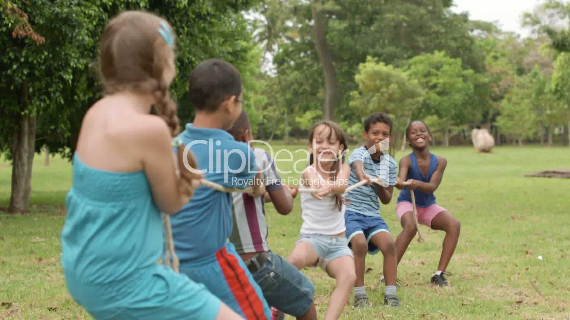 Happy school children playing tug of war in park: Royalty ...