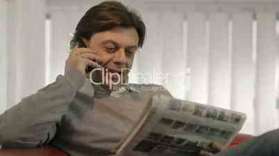 Happy businessman reading real estate ads on newspaper