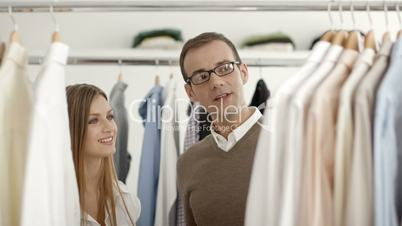 Man talking with sales assistant in clothes shop