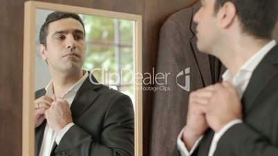Adult man dressing up and looking at mirror