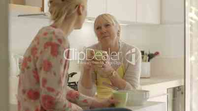 Mother and daughter talking, drinking coffee in kitchen at home