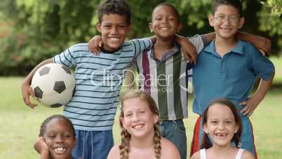 Group of boys and girls with soccer ball smiling