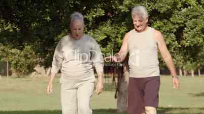 Old couple jogging and measuring blood pressure